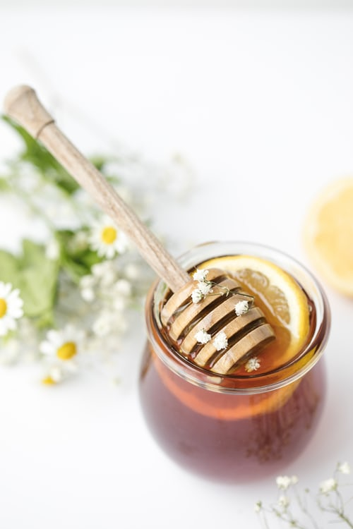 A beautiful Image of Honey in a bottle with a Spoon