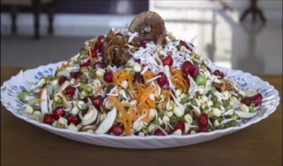 A plate full of fruit & nut sprout salad topped with pomegranate seeds, almond & cashew